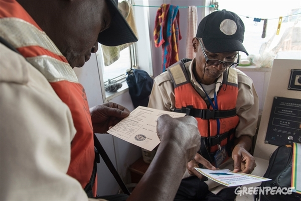 Guinean fishery inspectors on board Chinese fishing boat FU YUANG YU 362, checking licence and documents during a joint high sea operation with Greenpeace.