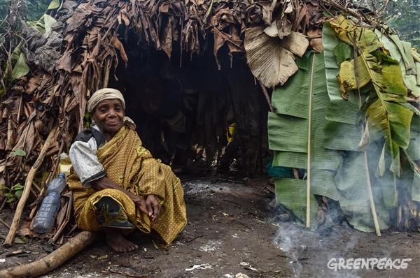 Indigenous Woman sitting next to a hut.