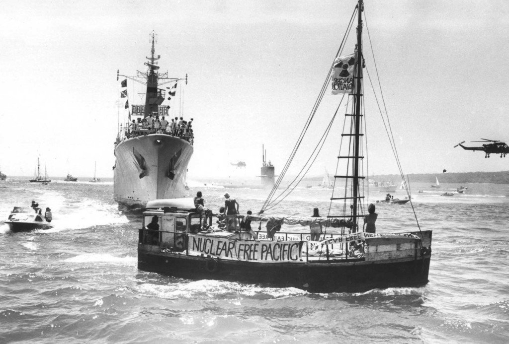 The USS Pintado submarine, escorted by the HMNZS Waikato (the same frigate sent to Moruroa test zone in 1973 by the New Zealand Government), is met by the Peace Squadron as it arrives in Waitemata harbour, Auckland in 1978. The vessel in the foreground is the Alliance - a scow which was part of the Peace Squadron. The growing anti-nuclear movement in New Zealand was hostile to visits from US ships because the Americans refused to confirm or deny whether their ships carried nuclear weapons. Public opinion was increasingly in favour of banning these visits. Between 1978 and 1983 opposition to nuclear-armed ship visits rose from 32% to 72%. In 1985 the Government effectively banned nuclear ship visits. New Zealand was the first country to declare itself nuclear free when it passed legislation in 1987.