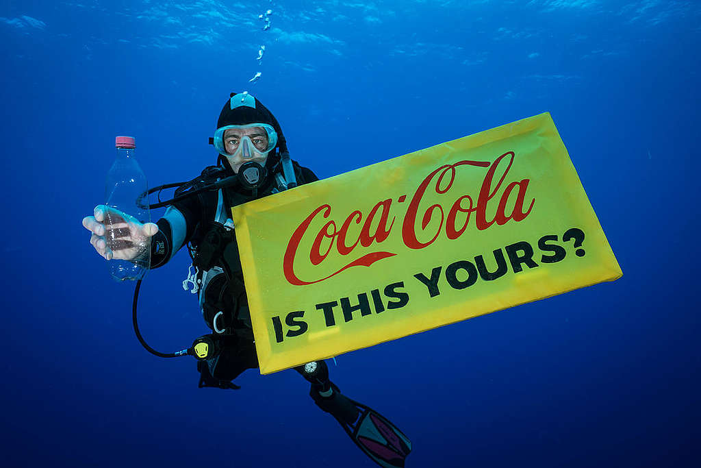 """A Greenpeace diver holds a banner reading """"Coca-Cola is this yours?"""" and a Coca-Cola bottle found adrift in the garbage patch."""