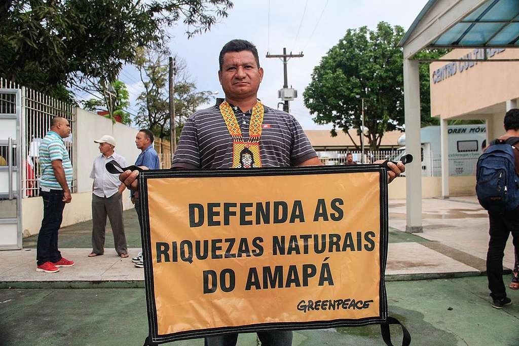 Cacique do povo Karipuna segura cartaz em defesa dos Corais da Amazônia.