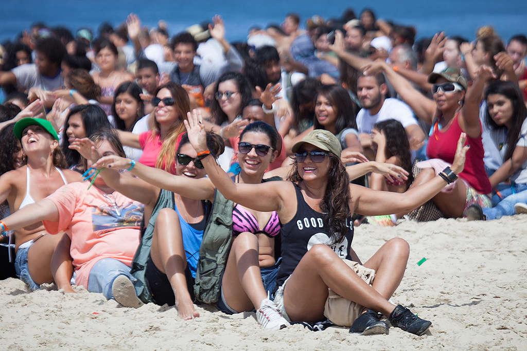 Pessoas sentadas na montagem do banner humano em defesa dos Corais da Amazônia.