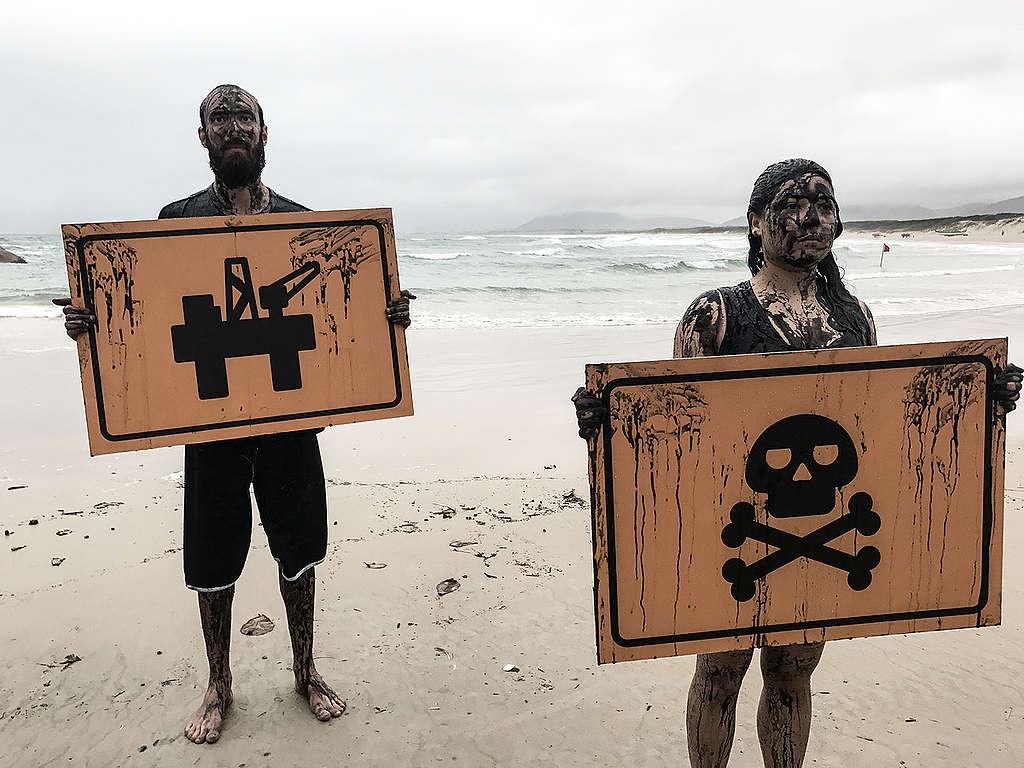 Voluntários sujo com petróleo falso do Greenpeace seguram placas com imagem de uma plataforma de petróleo e da morte.