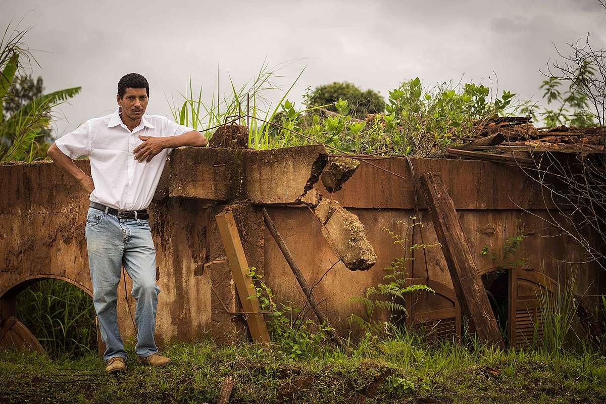 O apicultor Caé, ao lado de sua casa soterrada pela lama, em Bento Rodrigues.