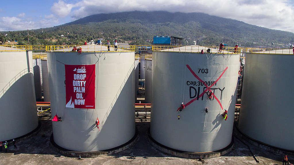 Ativistas abrem um imenso banner em cima de grandes tanques da refinaria da Wilmar. © Rendra Hernawan
