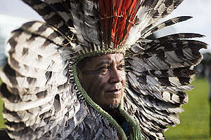 Indígena Kretã Kaingang com cocar de penas vermelhas e preto e brancas, sob a luz do sol em Brasília