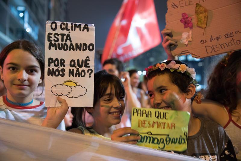"""meninas jovens seguram cartaz """"Se o clima está mudando, por que nós não?"""