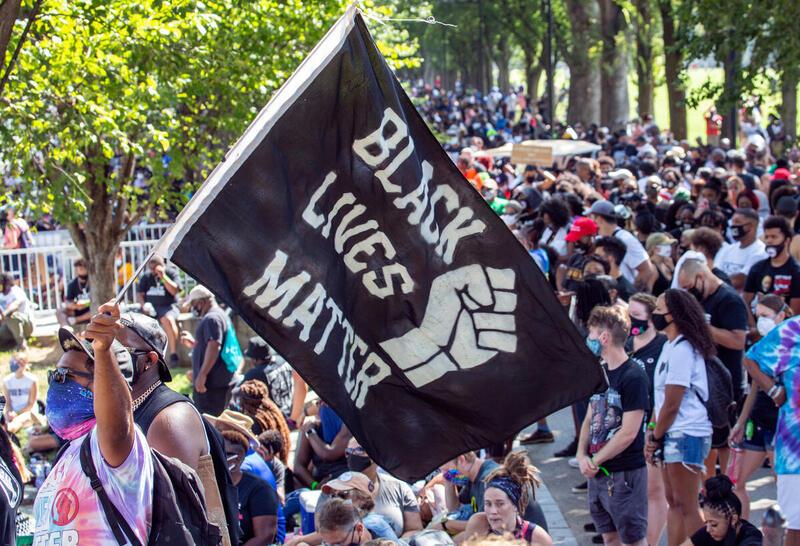 """marcha com bandeira dizendo Black lives matter"""" em Washington"""