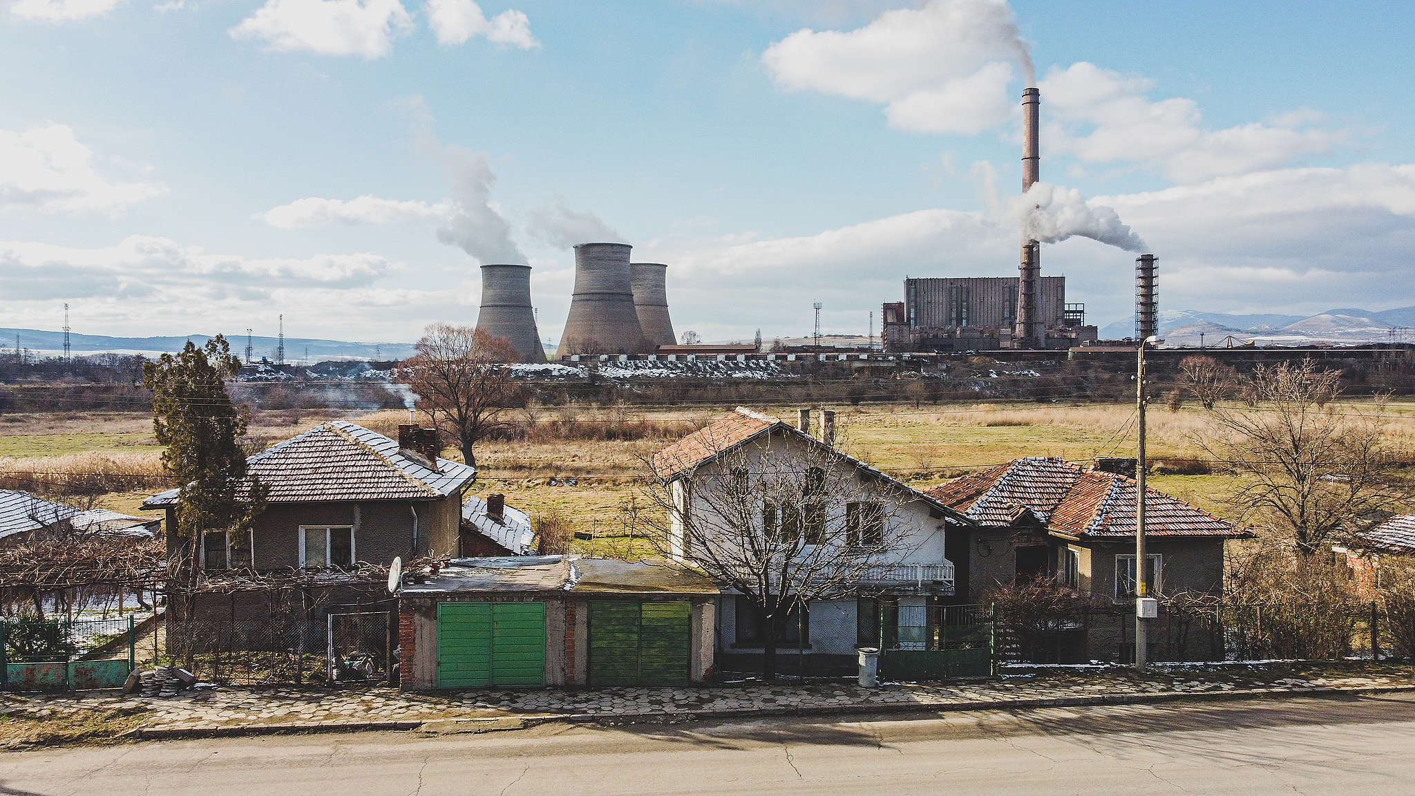"""ТЕЦ """"Бобов дол"""" изпуска непречистен емисии (от високия комин) по време на разпалване на инсталацията, въздушна снимка близо до къщи в Големо село, януари 2021 г."""
