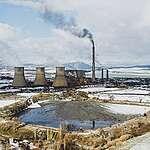 """ТЕЦ """"Бобов дол"""" изпуска непречистени емисии (от високия комин) по време на разпалване на инсталацията, на преден план е """"черното езеро"""" на централата, Големо село, януари 2021 г."""
