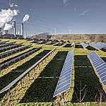 Соларни панели на фона на въглищна централа в Германия