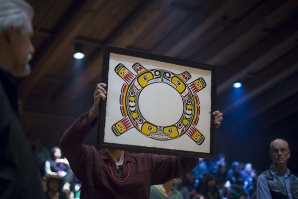 New Sisiutl Crest held aloft by Greenpeace staff Eduardo Sousa as Greenpeace foudners Rod Marining (left) and Bill Darnell (right) look on, at Willie Family Potlatch (Photo John Lehmann Globe And Mail)