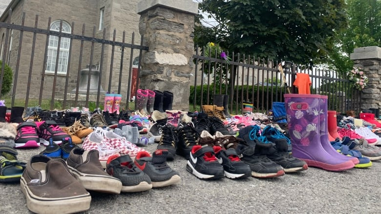 Children's shoes were placed in front of a church in Kahnawake, in memory of the 215 children whose remains were found in a mass grave at a residential school in Kamloops, British Columbia. (Chloe Ranaldi/CBC)