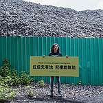 """Greenpeace Campaigner, Hall Sion Chan, is putting up a banner written """"Waste No More, Adequate Housing Now"""" in front of a few storey high waste mountain at Ha Tsuen, Hong Kong, urging the Government to seriously review the brownfield planning policy. © Greenpeace / Harry Long"""