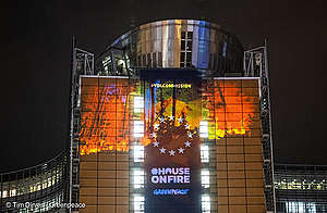 Projection of burning forests on the EU Commission. EU stars visible. #HouseOnFire / Greenpeace