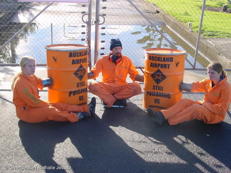 """Greenpeace activists (from left to right) Sarah Duthie, Steve Abel and Suzette Jackson in protest at the Auckland Airport.  Greenpeace blocked trucks of quarantine and medical waste from entering the incinerator at Auckland International Airport (AIAL). Three activists locked themselves to barrels bolted into the ground to prevent trucks from entering the site. Two more activists hung a banner on the building reading """"Stop Poisoning Us. Stop Incineration"""". Greenpeace demands that the facility will be replaced and that the New Zealand government bans incineration nationally. Dioxins are among the most poisonous substances known and there is no proven safe level of emissions. They are a by- product of the incineration process, and are not created by other waste disposal methods, such as steam sterilisation."""