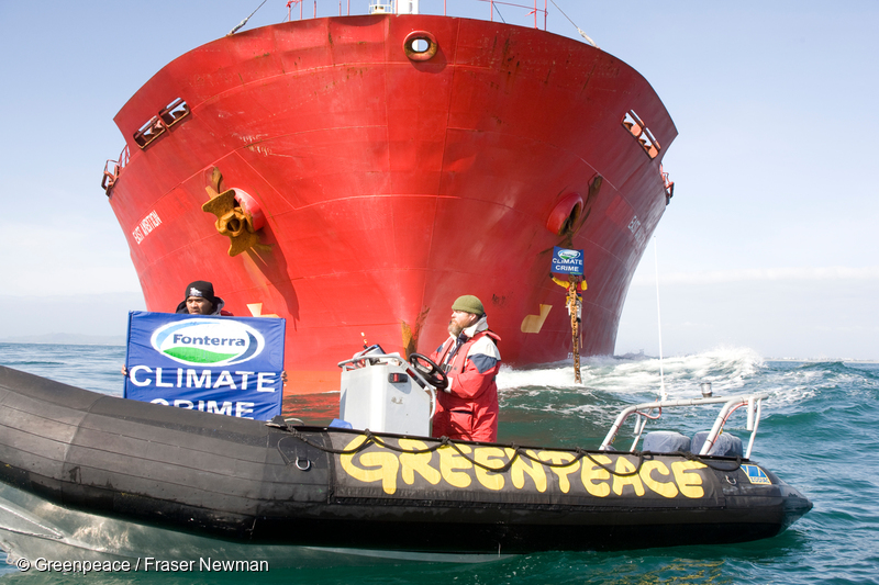 """Greenpeace activists on an inflatable hold a banner reading """"Climate crime"""", in front to the East Ambition cargo ship, while other activists are on board the ship blocking its shipment of palm kernel animal feed from Indonesia destined for Fonterra dairy farms."""
