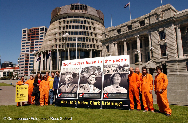 """Greenpeace activists with a billboard outside Parliament in Wellington, protesting the Labour-led Government's decision not to extend the GE moratorium. The billboard reads, """"Good leaders listen to the people"""" and depicts former prime ministers Norman Kirk and David Lange and current PM Helen Clark with historical images of anti-Vietnam, anti-nuclear and anti-GE protests corresponding to each PM, 23 October 2003"""