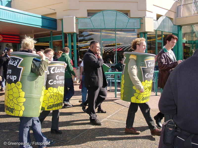 """Greenpeace activists protest against the government's cover up of a GE corn contamination. The activists followed Labour Party leader Helen Clark during the 2002 election campaign, dressed in corn cans labelled """"Clarkies' corn coverup""""."""