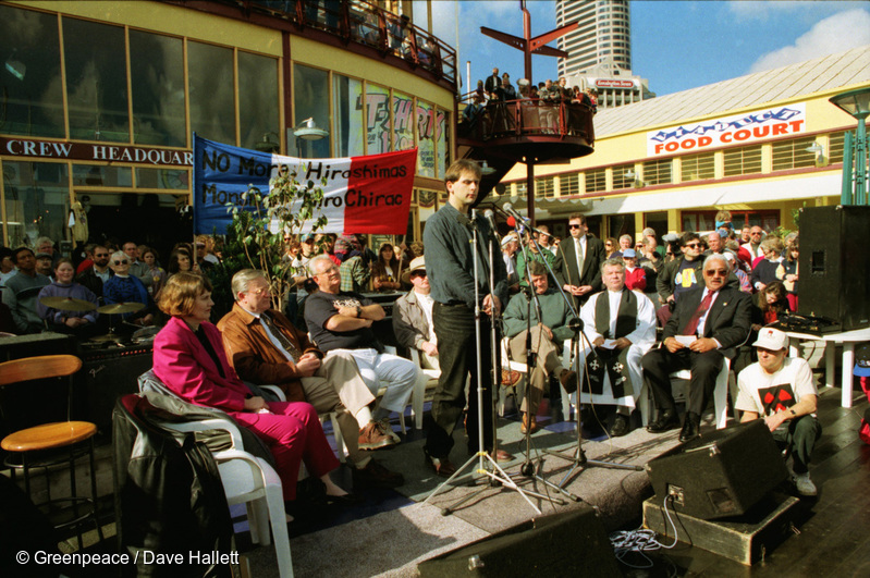 Michael Szarbo addresses crowd from stage. Michael Szabo of Greenpeace joins PM Jim Bolger and opposition leaders at public rally as a flotilla of small yachts leave Auckland bound for Moruroa to protest against French nuclear tests at the atoll.