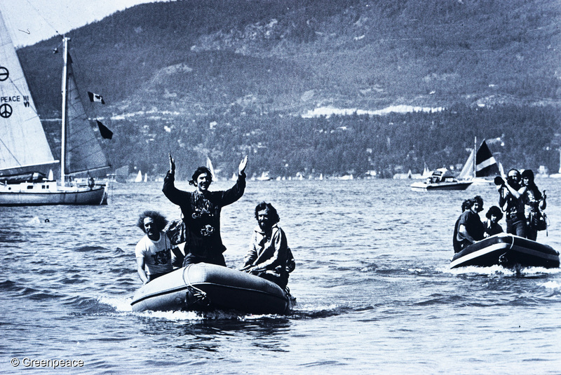 Rex Weyler (standing) with Bob Hunter on the right, as the Phyllis Cormack and crew return to Vancouver from the 1975 whale campaign. The Vega drifts in distance, to the left.