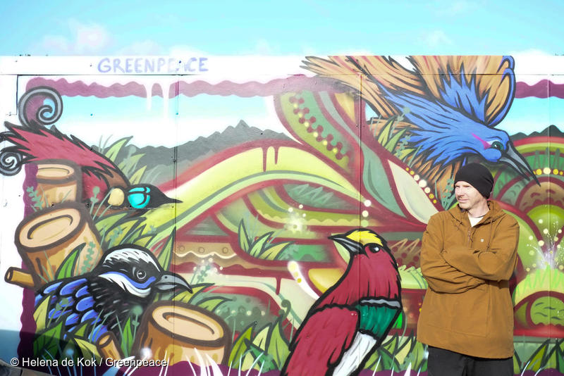 """Portrait of street artist Sean Duffell, in front of the mural he painted depicting birds of paradise in Wellington, New Zealand. Part of the Greenpeace event, 'Wings of Paradise"""" highlighting deforestation in the Indonesian province of West Papua."""