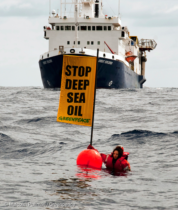 """Greenpeace activist Kylie Matthews (Ngāpuhi) next to a buoy holding a banner reading """"Stop deep sea oil"""" in front of the oil survey ship Orient Explorer to disrupt the seismic testing by Brazilian oil giant Petrobras in Raukumara Basin, off East Cape, North Island taken by Malcolm Pullman"""