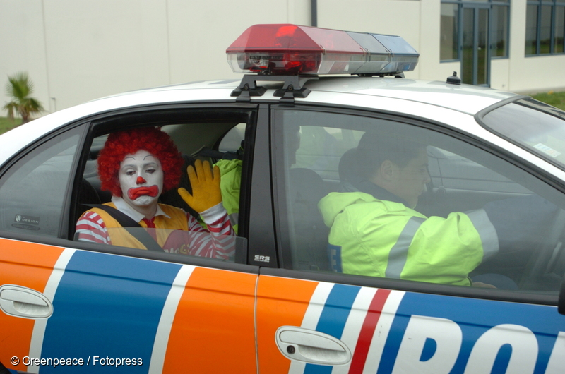 Greenpeace activist Gareth Hughes dressed as 'Ronald McDonald' being driven away by police after his arrest for chaining himself to the gates of McDonalds' distribution centre in Wiri, Auckland, 11 May 2004