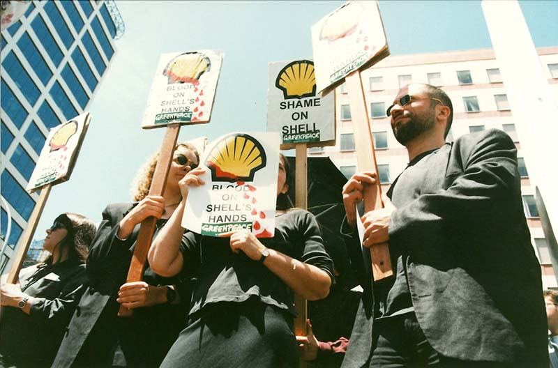 Greenpeace protested outside the Commonwealth Heads of Government Meeting in Auckland, opposing Shell's oil drilling on Ogoni land in the Niger Delta and its role in the judicial execution of Ken Saro-Wiwa. Pictured holding placards are Mana Tangata team members Nicola Easthope and Catherine Delahunty, and Antarctic campaign scientist Ricardo Roura. Photo: Glyn Walters
