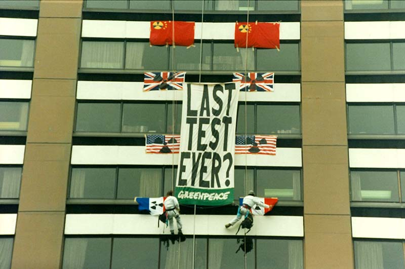 """27 January 1996: Greenpeace activists abseil down to the 8th floor of the building housing the French Embassy in Wellington to hang a large that reads """"Last Test Ever?"""" The 46-kiloton explosion carried out at Fangataufa Atoll near Moruroa Atoll in Te Ao Maohi/French Polynesia was a detonation of the 110-kiloton TN 75 thermonuclear warhead for France's M45 submarine-launched ballistic missile, which has a flight range of 6,000 kilometres. Photo: Rob Taylor"""