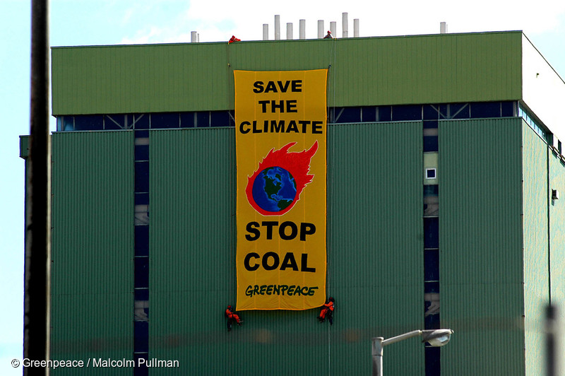 On the day the Kyoto Protocol comes into force, Greenpeace activists hang a banner reading 'Save the Climate  - Stop Coal' on Marsden B power station.  A proposed conversion would change this power station from oil to coal fired which will emit 2 million tonnes of climate changing carbon dioxide each year.