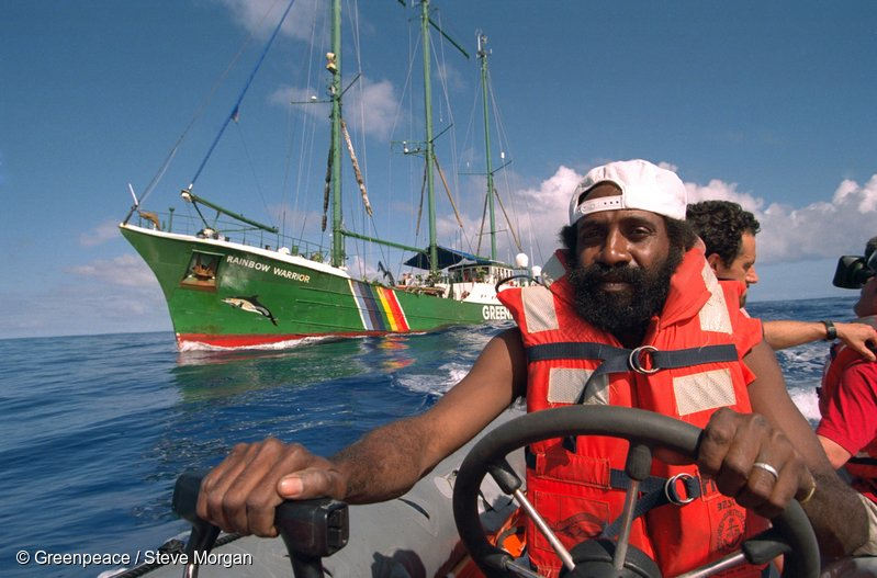 Rainbow Warrior crew member Philip Pupuka driving one of the inflatable boats flanked by SV Rainbow Warrior off Moruroa