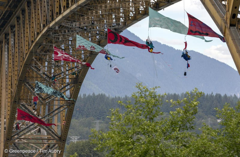 Activist form an aerial bridge blockade in the path of a Trans Mountain tar sands oil tanker traffic. The tar sands oil tanker was docked at the Kinder Morgan's Westridge Marine Terminal. The blockade is part of wave of growing resistance against the controversial Trans Mountain Expansion pipeline and tanker project (TMX). The activists suspended from the Iron Workers Memorial Bridge in Vancouver, British Columbia.