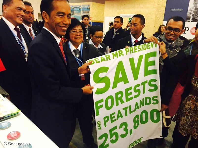 Indonesian President Joko Widodo, left, receives the petition banner from Greenpeace activists during the 21st Conference of Parties (COP21) at Stade de France in Paris, France, Nov.30, 2015. The petition is already signed by more than 253,800 people urging the President to save forest and peatlands in Indonesia. (Photo Greenpeace)