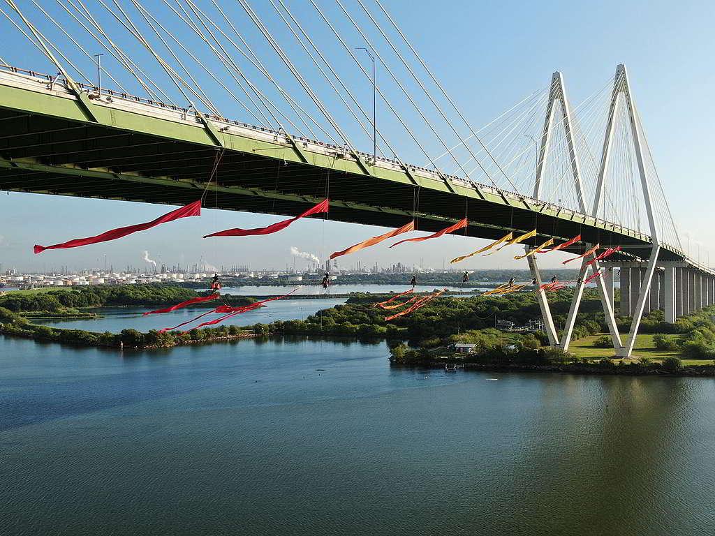 去年9月,22位綠色和平行動者垂吊於休斯敦Fred Hartman大橋,在這個化石燃料運輸幹道讓象徵可再生能源與可持續發展的旗幟飄揚。© Greenpeace