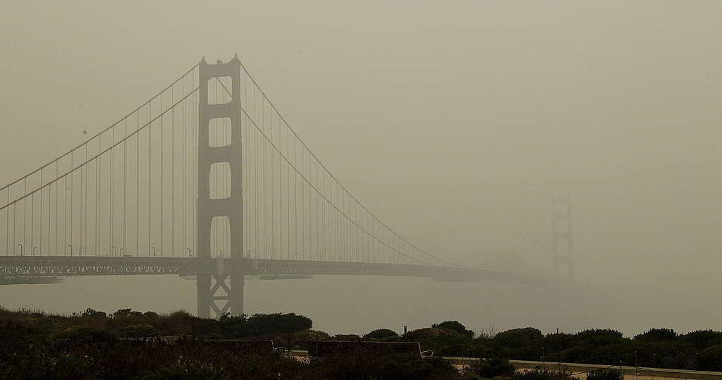 美國三藩市金門大橋的背景色從橙紅換上灰黃,代表當地居民續受煙霧與山火灰濃罩。 © George Nikitin / Greenpeace