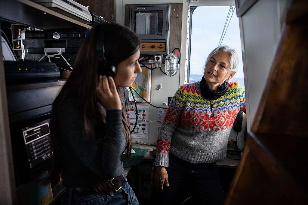年僅18歲的氣候行動者Mya-Rose Craig(左),在科學家Kirsten Thompson指導下以水聽器(hydrophone)追尋鯨魚與海豚聲蹤。 © Daniella Zalcman / Greenpeace