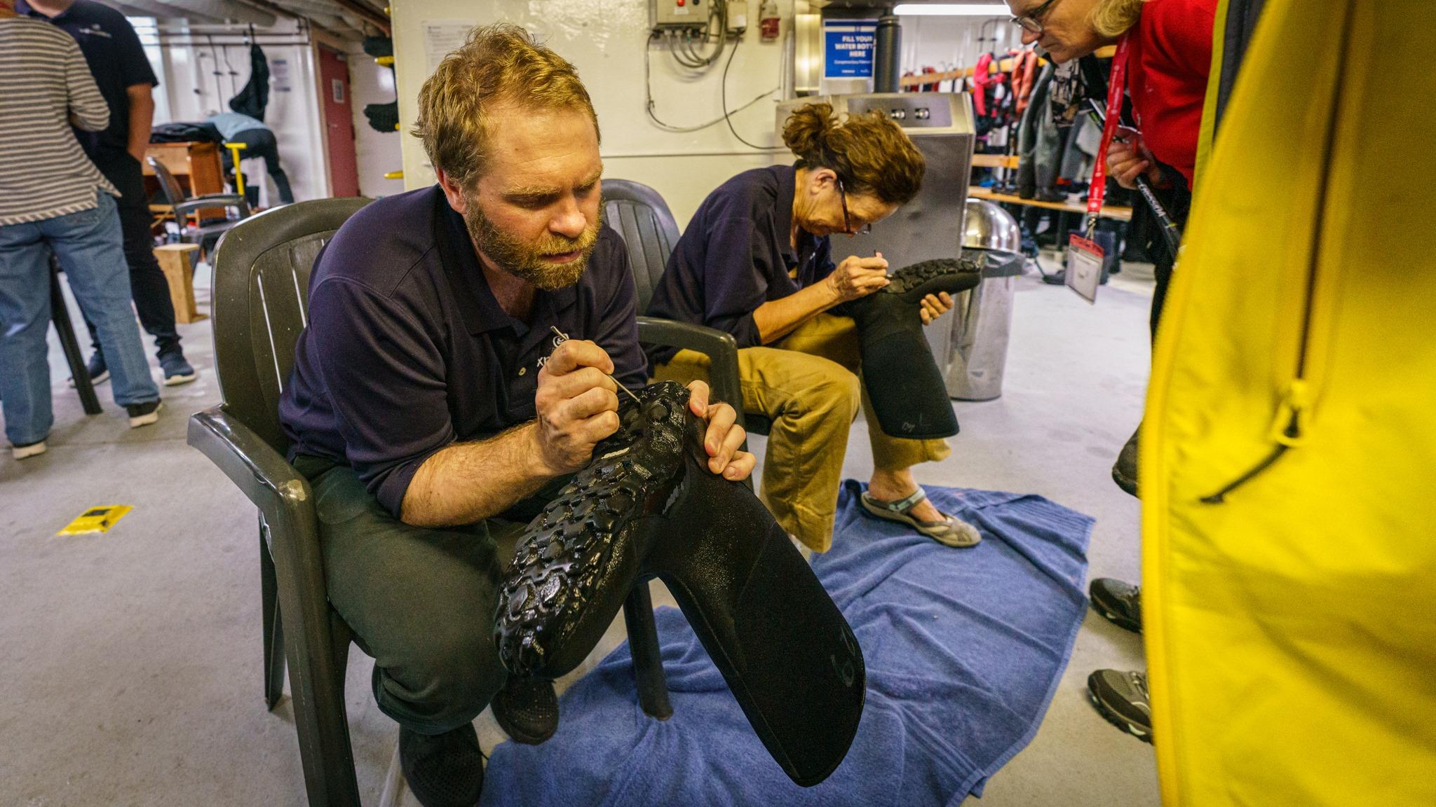 我們的探險隊長兼地質學家Alex Cowan 在登島前逐一檢查遊客的鞋底,若然發現任何異物,遊客必須再次消毒和清潔自己的鞋子。© Eric Wong / Greenpeace