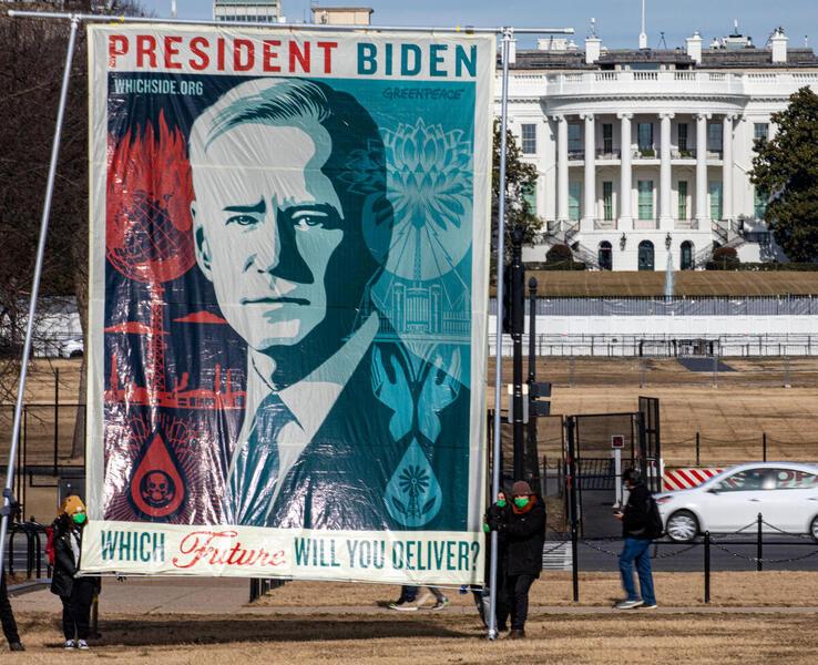 2021年1月27日美國華盛頓,綠色和平美國辦公室的行動者,竪起藝術家Shepard Fairey的畫作,要求總統拜登結束化石燃料種族主義時代,兌現「綠色新政」的承諾。© Tim Aubry / Greenpeace