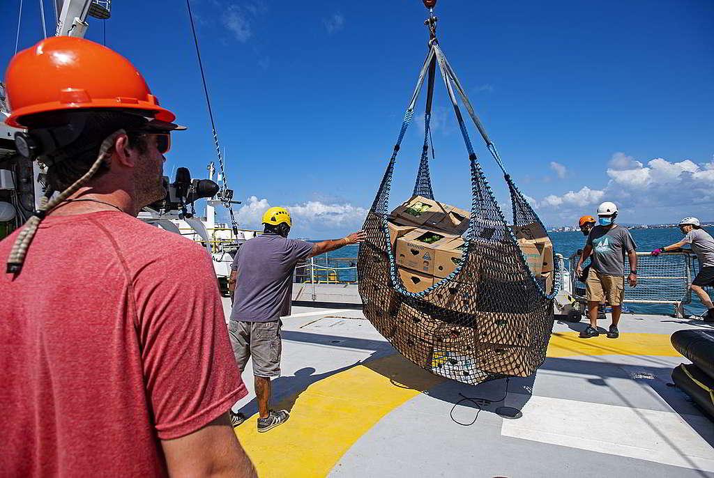 船員將食物從補給船上運送到彩虹勇士號,全員都要幫忙拆箱、搬運、收納3個月份量的食材。 © Marten van Dijl / Greenpeace