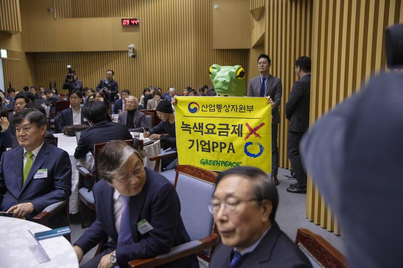 2019年綠色和平行動者戴著青蛙頭套,手持「綠色定價 X,企業 PPA O」的橫幅於國民議會會場默站,推動法案修定容許可再生能源供應商與用戶直接簽署購電協議(PPA)。© Soojung Do / Greenpeace