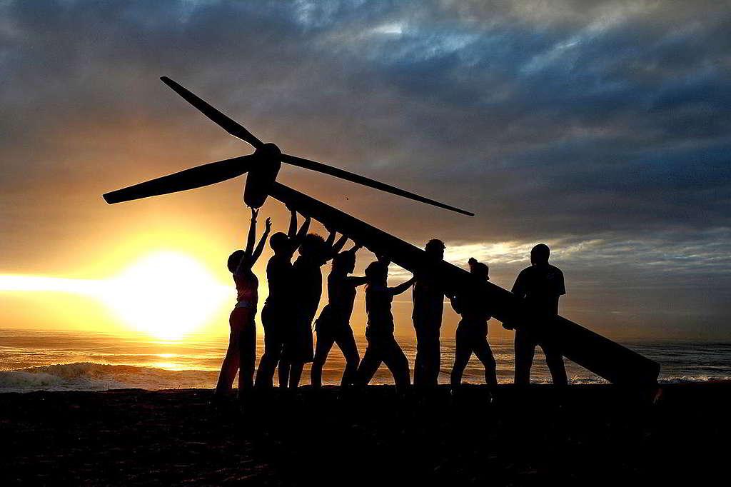35:2011年,聯合國氣候會議在南非德班舉行,綠色和平行動者與義工在附近一個沙灘豎立風車,喻意可再生能源晨曦將至。10年過去,加速淘汰化石燃料、轉型發展可再生能源漸成國際共識,綠色和平持續推動各國履行《巴黎氣候協定》莊嚴承諾,相信破曉時份指日可待。 © Shayne Robinson / Greenpeace