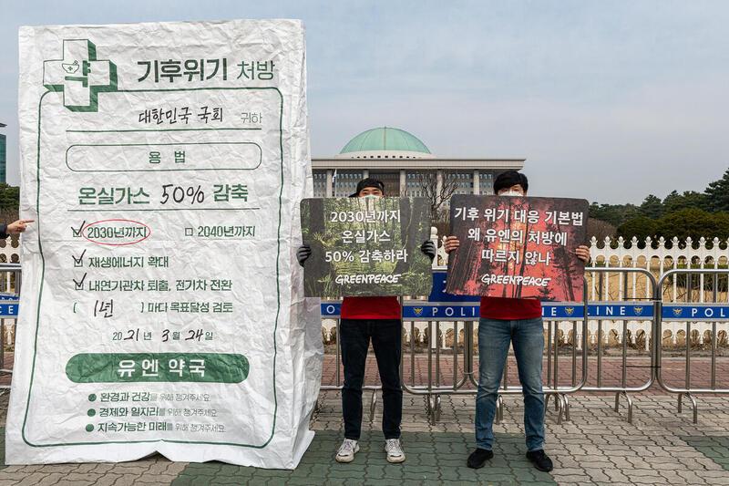 2021年3月綠色和平的行動者在韓國國會大樓前展示「氣候危機處方」,呼籲國會訂定「2030年將溫室氣體排放減半」等短期氣候策略,以達至韓國承諾2050碳中和的目標。© Greenpeace / Sungwoo Lee