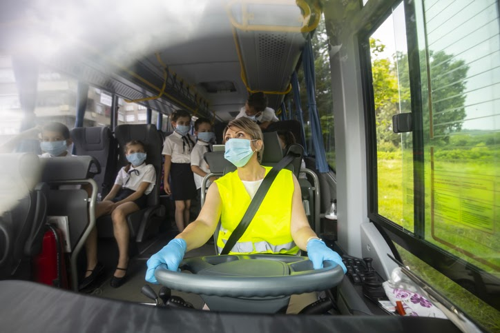 Bus driver driving school bus, wearing a face mask.