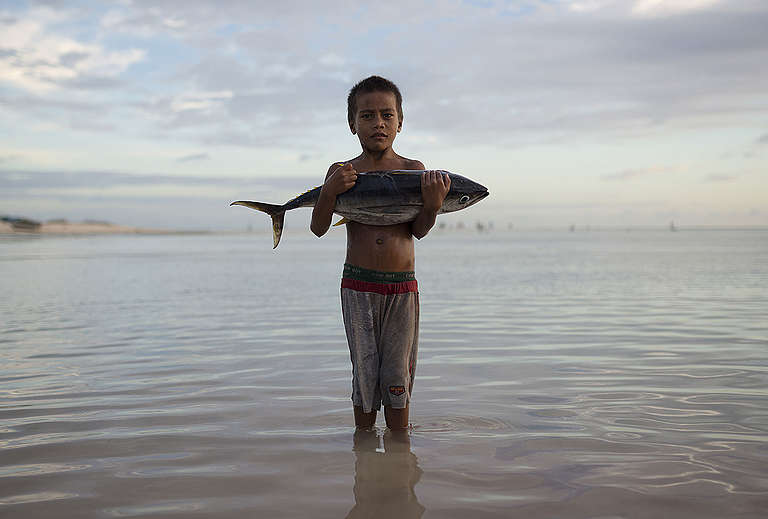 Boy with Tuna Fish Stands in Sea © Christian Åslund / Greenpeace