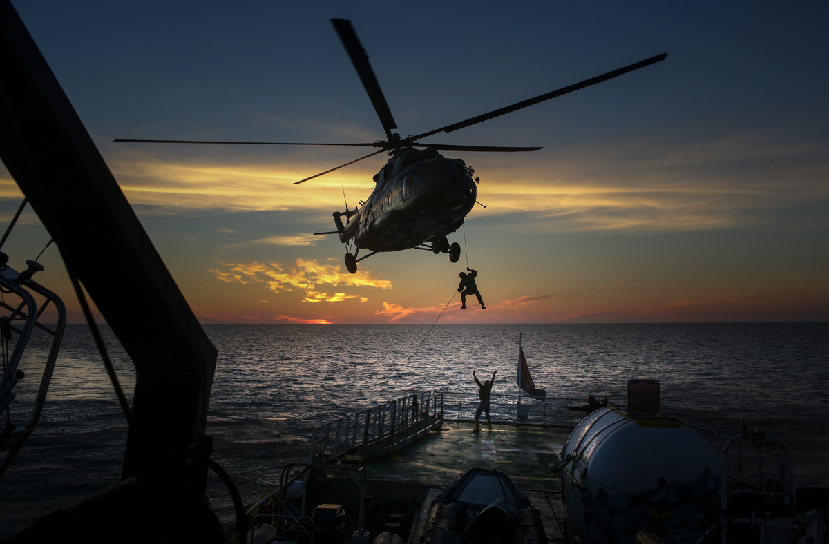 Armed Russian security services abseil from a helicopter onto the deck of the Arctic Sunrise (19 September, 2013).© Denis Sinyakov / Greenpeace