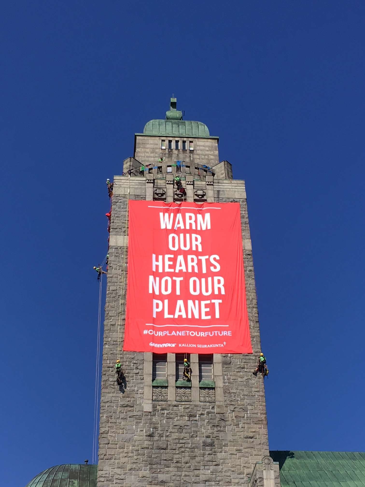 Greenpeace Nordic activists unfold two large banners in the high bell tower of Kallio church in Helsinki. © Greenpeace