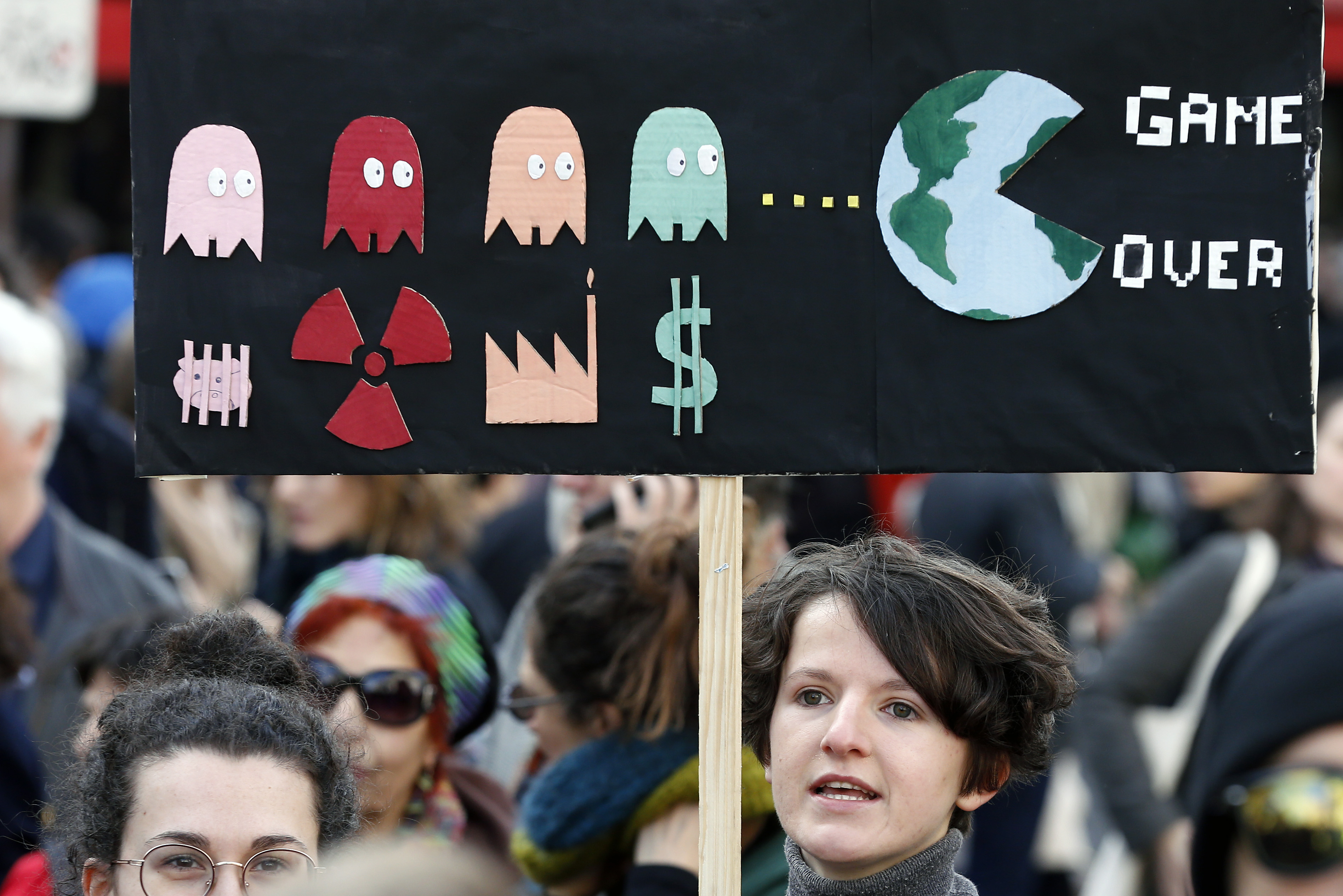"""PARIS, FRANCE - MARCH 16: A protester holds a sign reading """"Game over"""" as he takes part in the """"March of The Century"""" (La Marche du Siecle) to demand answers to climate change on March 16, 2019 in Paris, France. Several thousand people demonstrated in Paris to denounce the government's inaction on climate. Chesnot/Getty Images"""