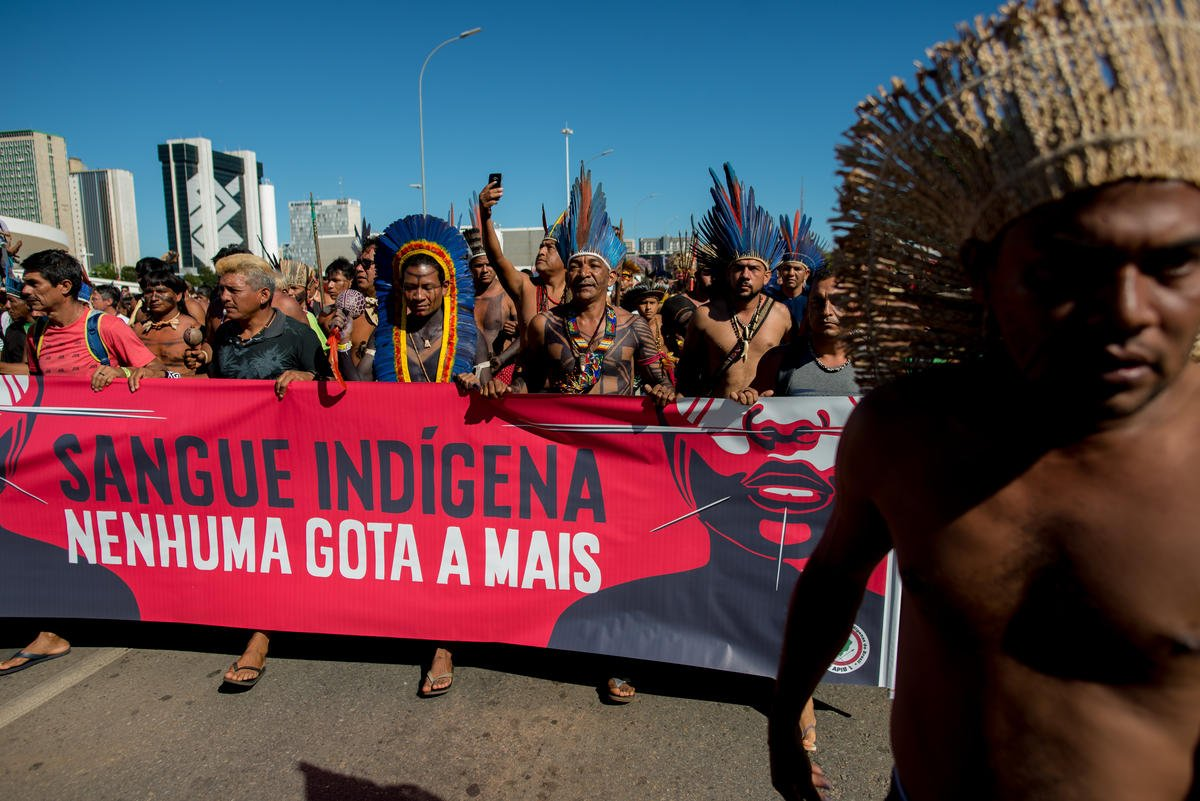 """Indigenous Peoples march in Brasília holding a sign saying """"Indigenous Blood - Not even one more drop"""". © Christian Braga / MNI"""