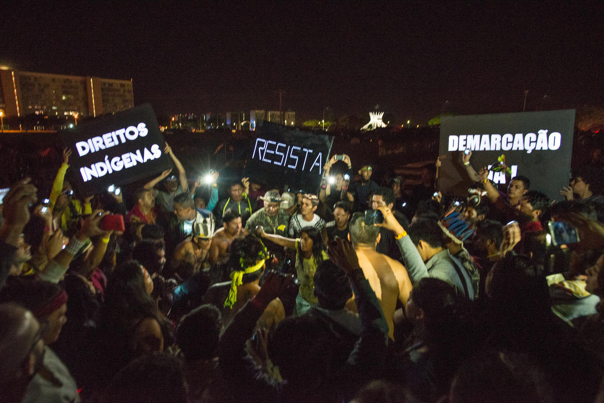 """Indigenous People hold """"Resist"""" signs and signs demanding the official recognition of the lands. © Christian Braga / MNI"""